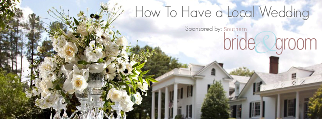 Different types of white flowers splaying out over a crystal vase with a historic white mansion in the background. Text